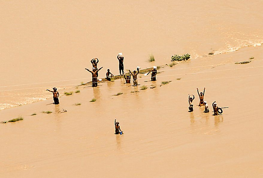 Pakistani villagers wave to Pakistan's Navy helicopter approaching a flooded area of Ghaus Pur near Sukkur, in Pakistan's Sindh province, Wednesday, Aug. 11, 2010. The U.N., relying on Pakistani figures, says the number of people affected by flooding over the past two weeks is 13.8 million, more than the combined total of the 2004 Indian Ocean tsunami, the 2005 Kashmir earthquake and the 2010 Haiti earthquake, although the death toll in each of those disasters was much higher than the 1,500 people killed in the floods. (AP Photo/Shakil Adil)