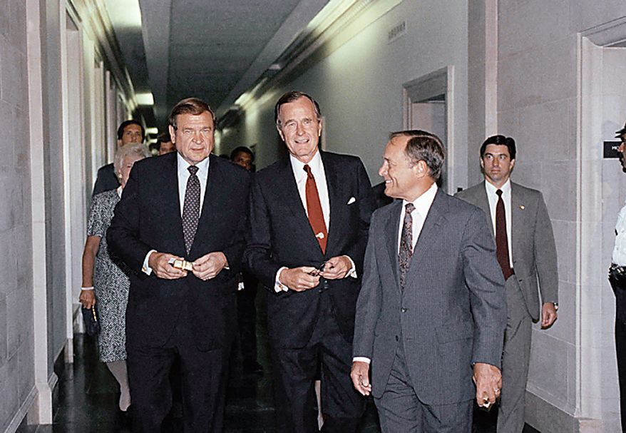 U.S. President George H. Bush waves to photographers as he walks with Reps. Dan Rostenkowski, D-Ill., chairman of the House Ways and Means Committee, left; and Bill Archer, R-Texas, ranking Republican on the same committee, right, on Capitol Hill in Washington, Monday, July 24, 1989. Bush attended the committee's Capitol Hill dinner. At far left is first lady Barbara Bush. (AP Photo/Ron Edmonds)
