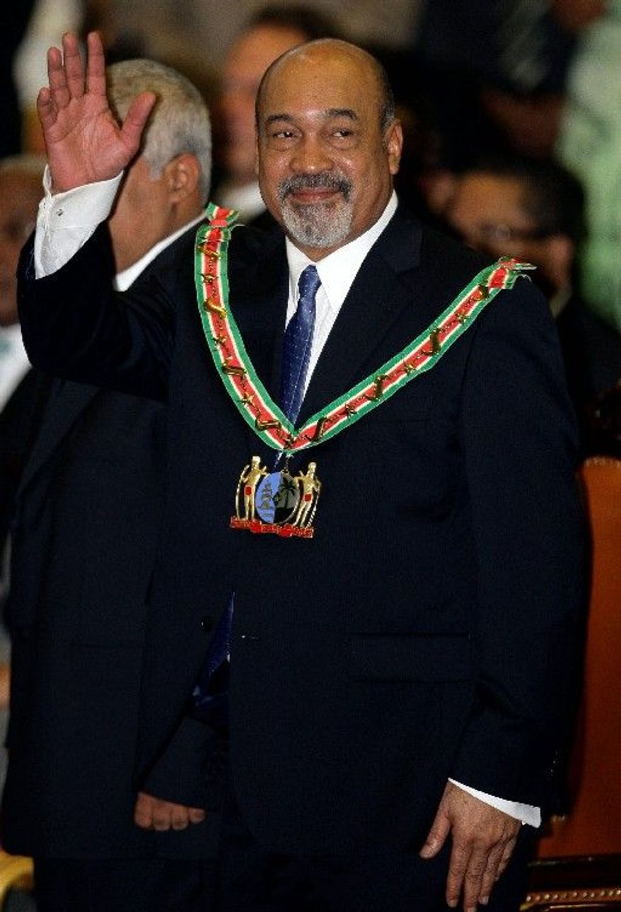 ASSOCIATED PRESS Suriname's President Desi Bouterse waves Thursday after his swearing-in in Paramaribo. The former coup leader is a convicted drug trafficker and accused murderer.