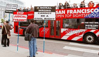 Tourists take photos of gay-marriage foes on Thursday in San Francisco. Federal Judge Vaughn Walker gave opponents of same-sex weddings until Aug. 18 to get an injunction from a three-judge appeals court panel to block his ruling allowing the resumption of gay marriages.