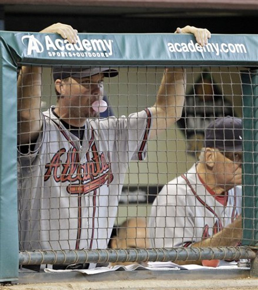Atlanta Braves third baseman Chipper Jones, left, is helped off the field by head trainer Jeff Porter, right, after being injured while fielding a ground ball and throwing to first base during the sixth inning of a baseball game against the Houston Astros Tuesday, Aug. 10, 2010 in Houston. (AP Photo/David J. Phillip)