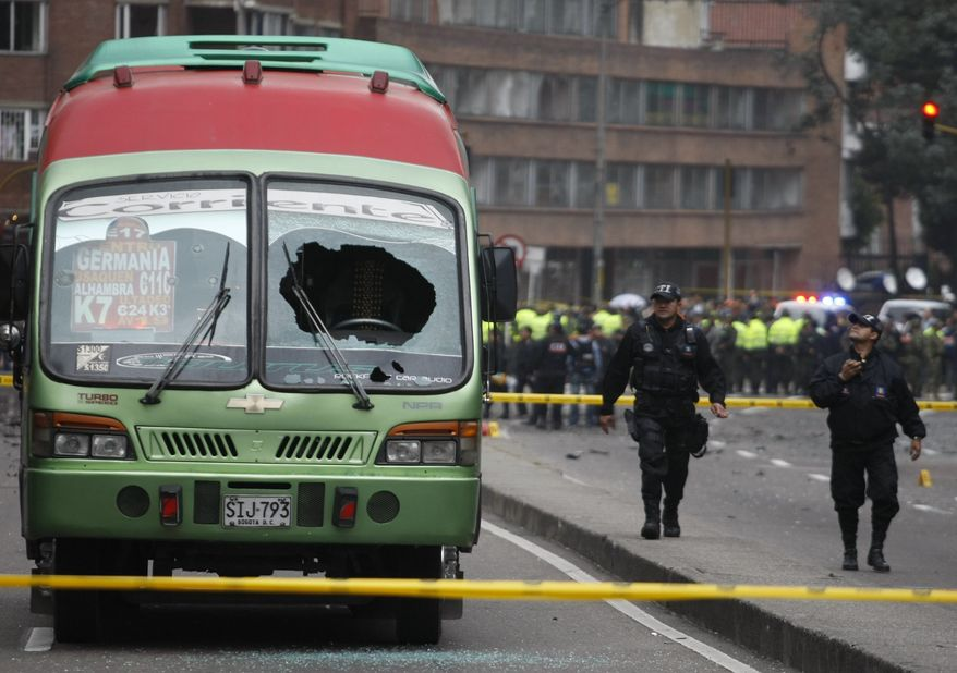 Agents from the police anti-explosive unit walk next to a damaged public bus near the scene of a car bomb explosion outside the Caracol Radio station in Bogota, Colombia, on Thursday, Aug. 12, 2010. The explosion injured at least nine people, police said. No deaths were reported. (AP Photo/William Fernando Martinez)