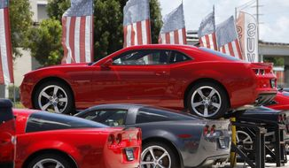 A 2010 Chevrolet Camaro RS is on display above a row of 2010 Corvettes at Kendall Chevrolet in Miami on Thursday, Aug. 5, 2010. (AP Photo/Lynne Sladky)
