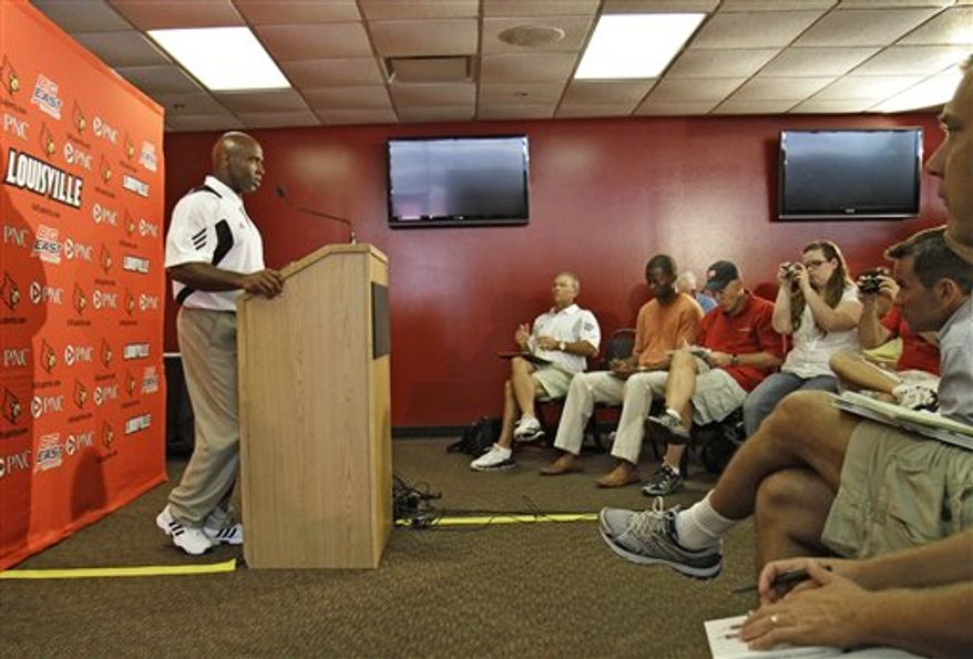 First-year Louisville head coach Charlie Strong, left,  jokes with graduate assistant Tommy Restivo during a coaching staff group photo session during NCAA college football media day activities for the University of Louisville in Louisville, Ky., Tuesday, Aug. 10, 2010.  (AP Photo/Garry Jones)
