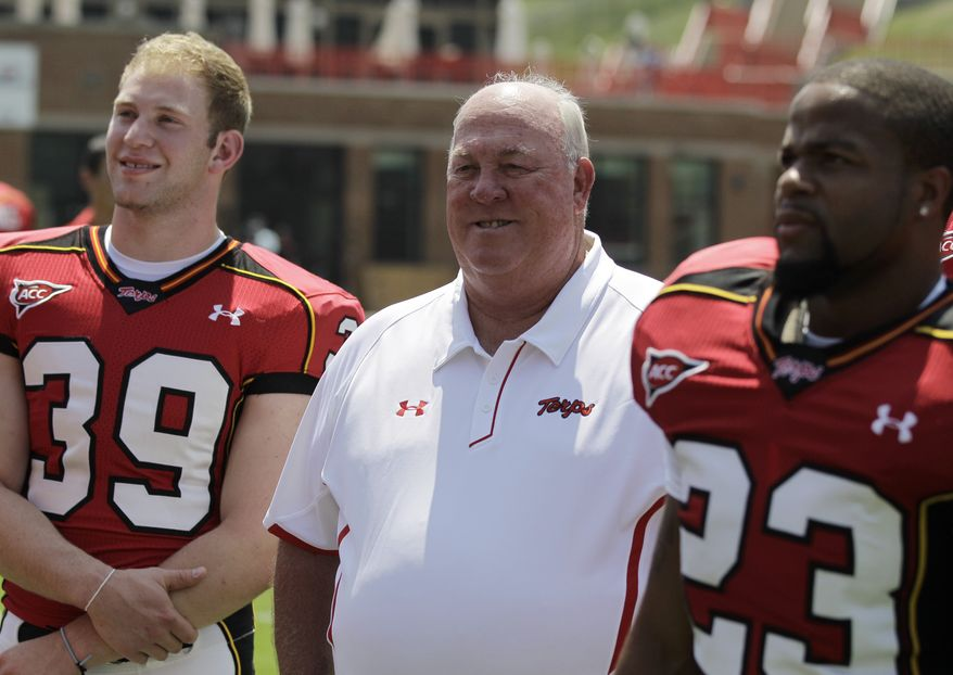 ASSOCIATED PRESS Maryland head football coach Ralph Friedgen, center, waits to have his photograph made with players Steffan Lazerow (39) and Da'Rel Scott (23) during the football team's media day, Tuesday, Aug. 10, 2010, in College Park, Md.