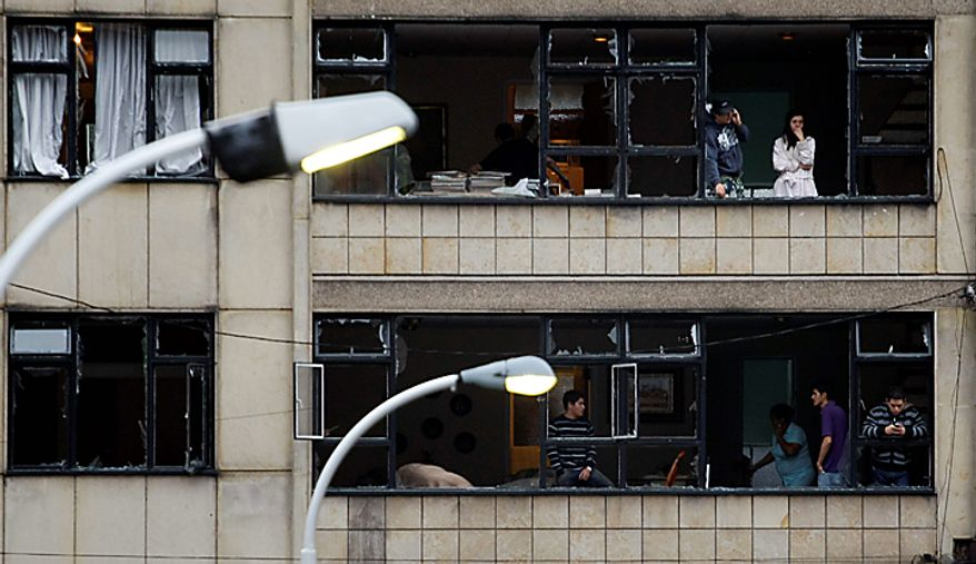 People look through damaged windows after a car bomb exploded outside the building of Caracol Radio in Bogota, Colombia, Thursday, Aug. 12, 2010.  The explosion shook Colombia's capital on Thursday, injuring at least six people, police said. No deaths were reported. (AP Photo/William Fernando Martinez)
