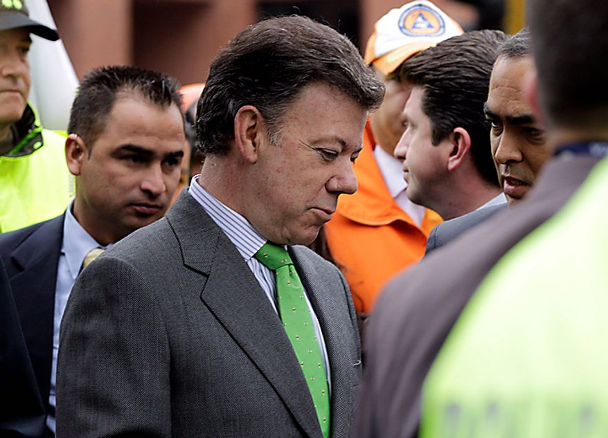 Colombia's  President Juan Manuel Santos, left, arrives at the scene where a car bomb exploded outside the building of Caracol Radio station in Bogota, Colombia, Thursday, Aug. 12, 2010. The explosion shook Colombia's capital on Thursday, injuring at least six people, police said. No deaths were reported.  (AP Photo/William Fernando Martinez)