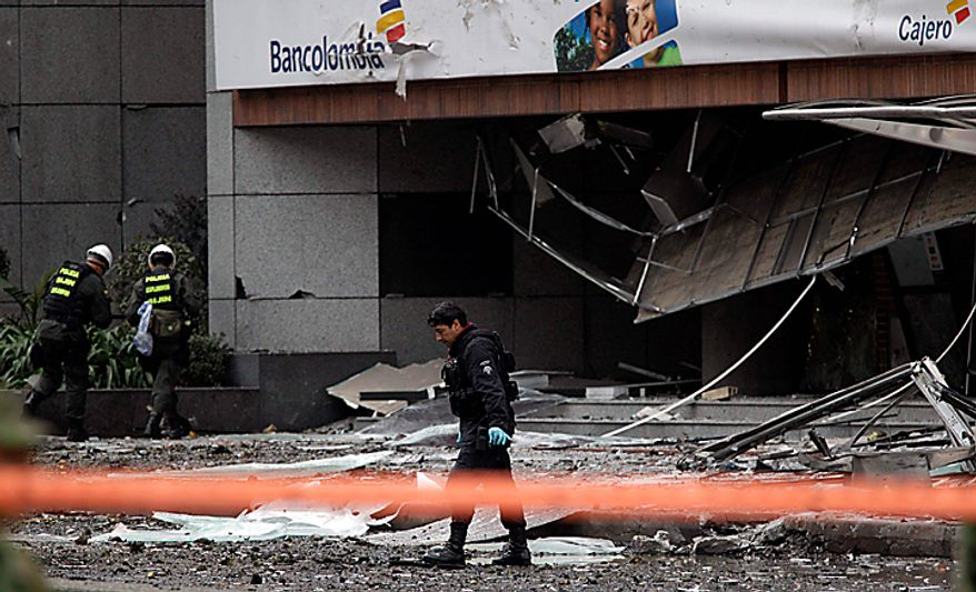 Agents, from the police anti explosive unit, collect evidence at the scene of a car bomb explosion outside the building of Caracol Radio station in Bogota, Colombia, Thursday, Aug. 12, 2010. The explosion shook Colombia's capital on Thursday, injuring at least six people, police said. No deaths were reported. (AP Photo/Fernando Vergara)