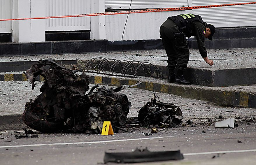 An anti explosive expert collects evidence next to the wreckage of a car bomb that exploded  outside the building of Caracol Radio station in Bogota, Colombia, Thursday, Aug. 12, 2010.  The car bomb explosion outside a major radio station shook Colombia's capital on Thursday, injuring at least six people, police said. No deaths were reported. (AP Photo/Fernando Vergara)