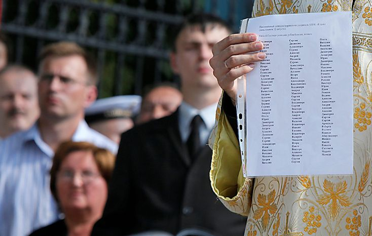 A clergyman of the St. Nicolas Cathedral holds  list of submarine disaster victims in St.Petersburg, Russia, Thursday, Aug. 12, 2010. Russian navy ships are flying flags at half-mast and memorial ceremonies are