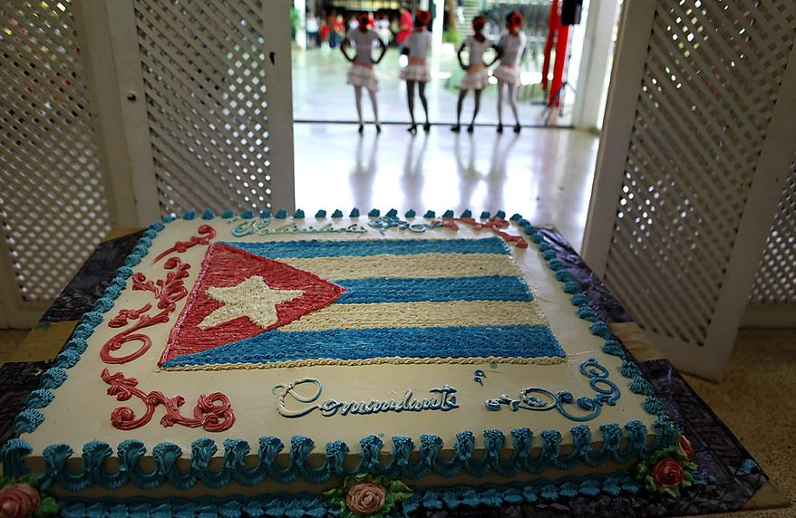 "A cake decorated with a Cuban flag that reads in Spanish ""Congratulations Commander"" sits on display as children perform at an event honoring Fidel Castro's 84th birthday at the Ernesto ""Che"" Guevara Palace of Pioneers in Havana, Cuba, Friday Aug. 13, 2010. (AP Photo/Javier Galeano)"