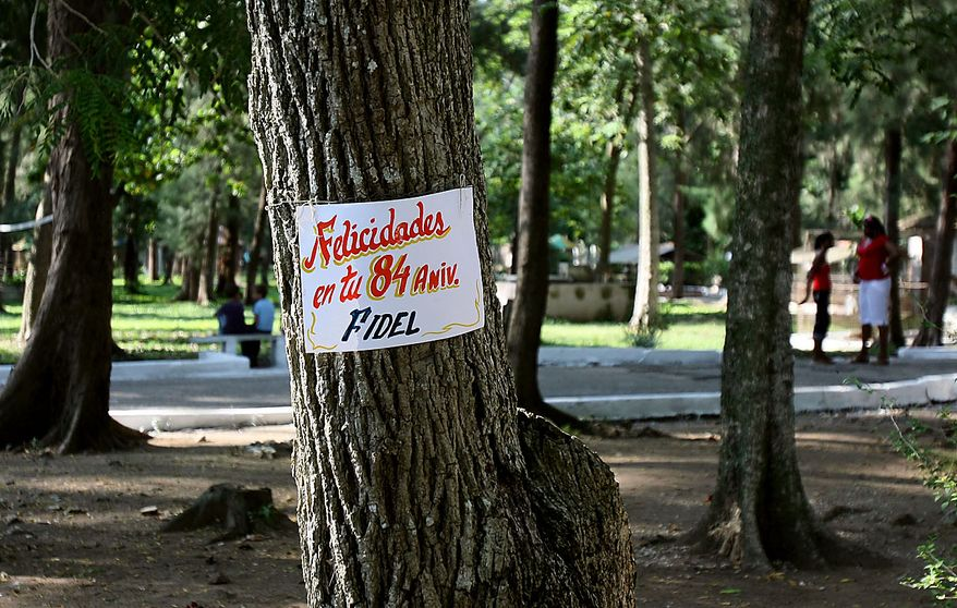 """A sign that reads in Spanish """"Congratulations on your 84th birthday Fidel"""" hangs on a tree in Sancti Spiritus, Cuba, Friday Aug. 13, 2010.  Fidel Castro turns 84 on Friday. (AP Photo/Ismael Francisco, Prensa Latina)"""