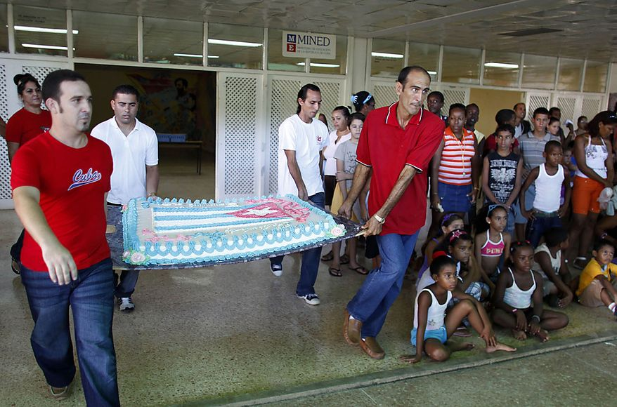 """People carry a cake at an event celebrating Fidel Castro's 84th birthday at the Ernesto """"Che"""" Guevara Palace of Pioneers in Havana, Cuba, Friday Aug. 13, 2010. (AP Photo/Javier Galeano)"""