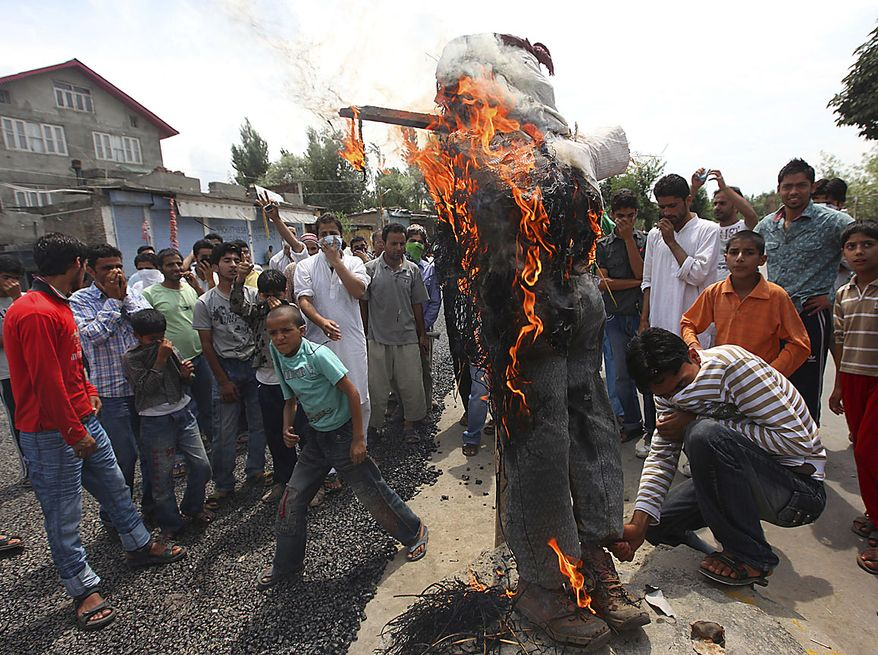 Kashmiri protesters look on as they burn an effigy representing Indian Prime Minister Manmohan Singh, during a protest in Srinagar, India, Friday, Aug. 13, 2010. Government forces fired at hundreds of anti-India protesters for defying a curfew in the Indian portion of Kashmir on Friday, killing a teenage student and injuring a few others, police said.(AP Photo/Dar Yasin)
