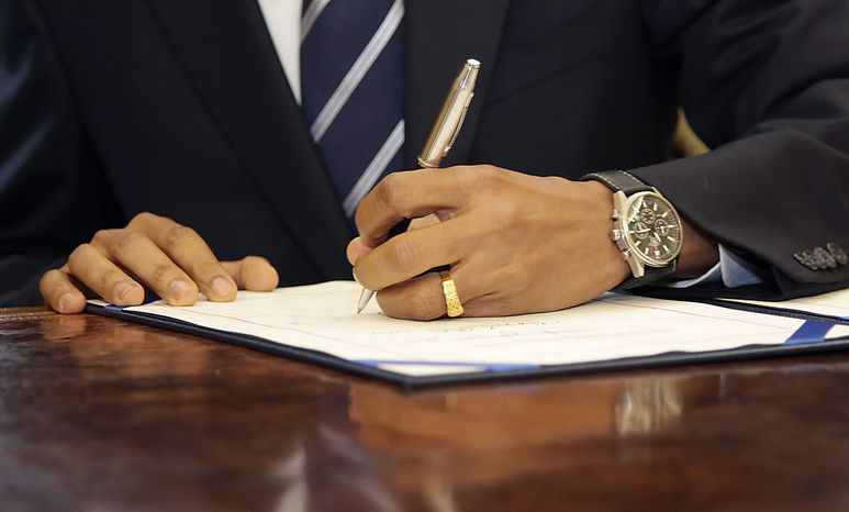 President Barack Obama signs the Southwest Border Security Bill, Friday, Aug. 13, 2010, in the Oval Office of the White House in Washington. (AP Photo/Carolyn Kast