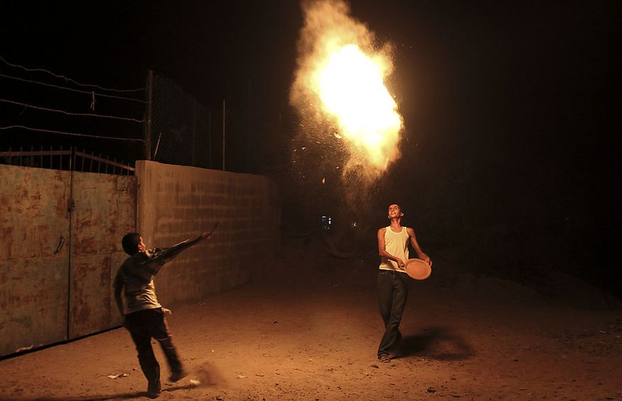 Palestinian boys play with fireworks, during the Muslim holy fasting month of Ramadan in the Shati refugee camp in Gaza City, Thursday, Aug. 12, 2010. Devout Muslims refrain from eating, drinking and smoking from dawn to dusk during Ramadan, a time of heightened religious fervor. (AP Photo / Hatem Moussa)