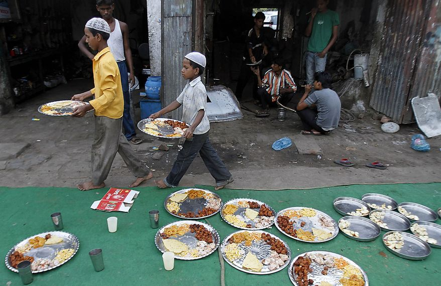 Young Indian Muslim mechanics carry food for iftaar, meal that breaks a day-long fast, during the first day of holy month of Ramadan, in Allahabad, India, Thursday, Aug. 12, 2010. Devout Muslims refrain from eating, drinking and smoking from dawn to dusk during Ramadan, a time of heightened religious fervor. (AP Photo/Rajesh Kumar Singh)