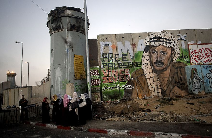 Palestinian women wait near a section of Israel's separation barrier covered in graffiti, one depicting the late Palestinian leader Yasser Arafat, at the Kalandia checkpoint , between Jerusalem and the West Bank city of Ramallah, Friday, Aug. 13, 2010. Israel loosened some restrictions on Palestinian movement between the West Bank and Israel during the monthlong Muslim fasting month of Ramadan.(AP Photo/Sebastian Scheiner)