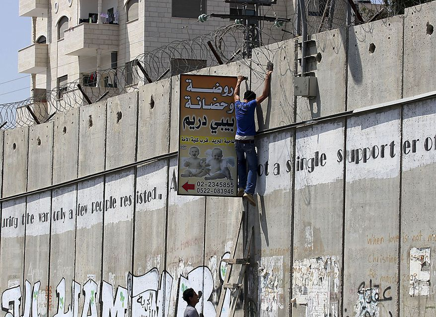 Palestinians climb a ladder to cross Israel's separation barrier into Jerusalem, in the West Bank town of Aram, Friday Aug. 13, 2010. Israel loosened some restrictions on Palestinian movement between the West Bank and Israel during the monthlong Muslim fasting month of Ramadan.(AP Photo/Nasser Ishtayeh)