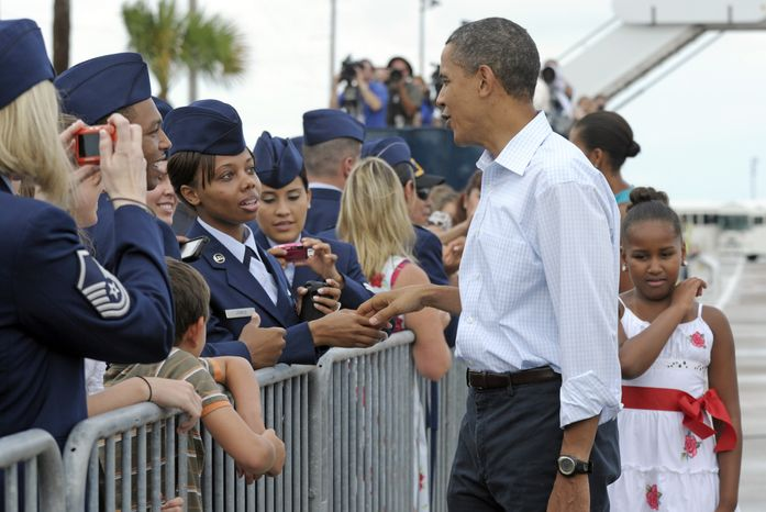 President Barack Obama, first lady Michelle Obama, partially visible second from right, and daughter Sasha, right, greet people at Tyndall Air Force Base in Panama City, Fla, Saturday, Aug. 14, 2010, upon their arrival. The Obamas are spending the weekend in Florida. (AP Photo/Susan Walsh)