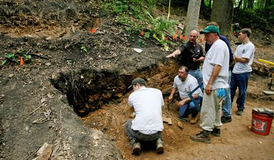 Frank Watson (second left kneeling) and William Watson (second right standing) survey the site that they think is a mass grave for immigrant Irish railroad workers in Malvern, Pa. Continuing field work seems to indicate some were killed not by cholera but by human hands. Despite their lack of archaeological experience, historians at Immaculata University are leading the excavation in suburban Philadelphia. (Associated Press)