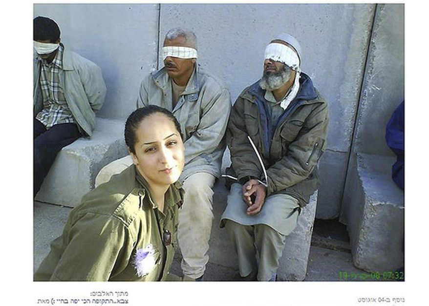 In this undated photo, originally posted on a Facebook page belonging to Eden Aberjil, and taken from the Israeli blog site sachim.tumblr.com, an Israeli army soldier poses in front of blindfolded men identified in the Israeli new media as Palestinian prisoners. Israeli news media and bloggers have identified the soldier in the photos as Aberjil. (AP Photo/sachim.tumblr.com)