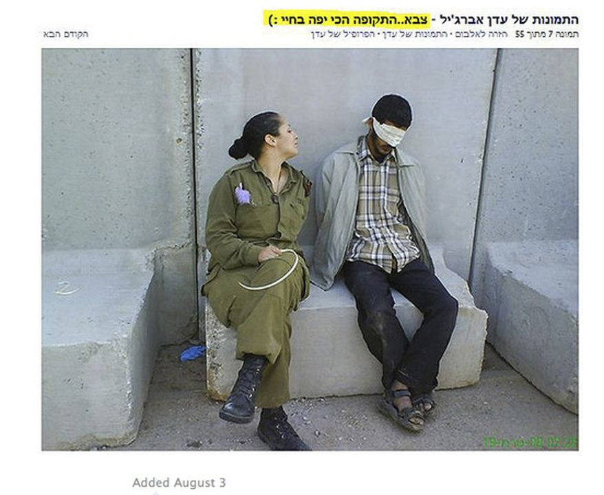 """In this undated photo, originally posted on a Facebook page belonging to Eden Aberjil, and taken from the Israeli blog site sachim.tumblr.com, an Israeli army soldier poses in front of blindfolded men identified in the Israeli media as Palestinian prisoners. The Hebrew in the top right translates as, """"Eden Arberjil's photos - army...the best time of my life."""" Israeli news media and bloggers have identified the soldier in the photos as Aberjil. (AP Photo/sachim.tumblr.com)"""