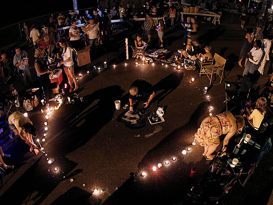Chris Drummond, of Sydney, Australia, draws a portrait of Elvis Presley on Elvis Presley Boulevard in front of Graceland, Presley's Memphis, Tenn., home, on Sunday, Aug. 15, 2010. Elvis Presley fans from around the world flocked to Graceland on Sunday for the annual late night procession past the king of rock 'n' roll's grave. Presley died at his Graceland mansion Aug. 16, 1977. (AP Photo/Mark Humphrey)
