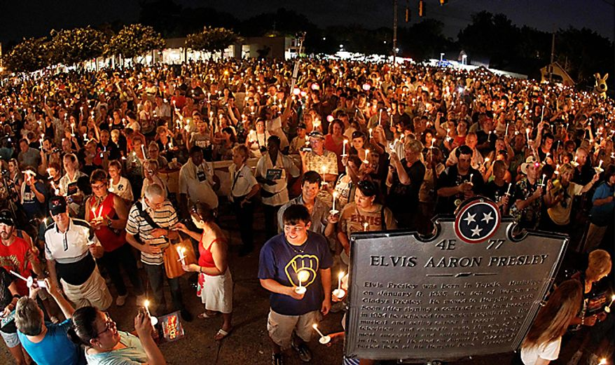 Elvis Presley fans hold candles on Elvis Presley Boulevard outside Graceland, his Memphis, Tenn., home, on Sunday, Aug. 15, 2010. Elvis Presley fans from around the world flocked to Graceland on Sunday for the annual late night procession past the king of rock 'n' roll's grave. Presley died at his Graceland mansion Aug. 16, 1977. (AP Photo/Mark Humphrey)