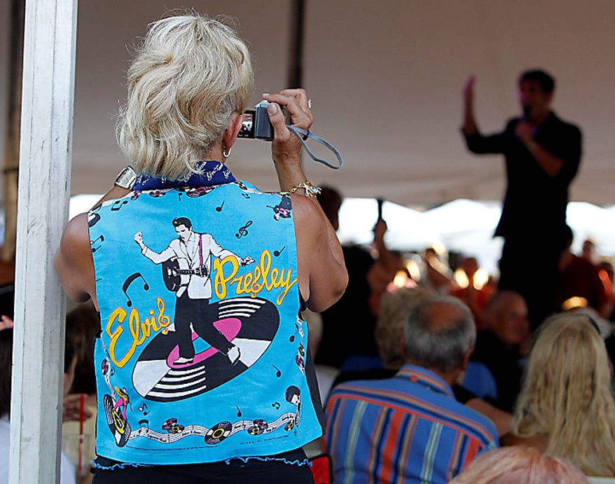 Stella Drummond, left, of Sydney, Australia, films an Elvis Presley impersonator on Sunday, Aug. 15, 2010, in Memphis, Tenn. Ms. Drummond came to Graceland on her honeymoon and has been back every year since. Presley fans from around the world are at Graceland for the annual nighttime procession past his grave on the eve of his death. Presley died at the home Aug. 16, 1977. (AP Photo/Mark Humphrey)