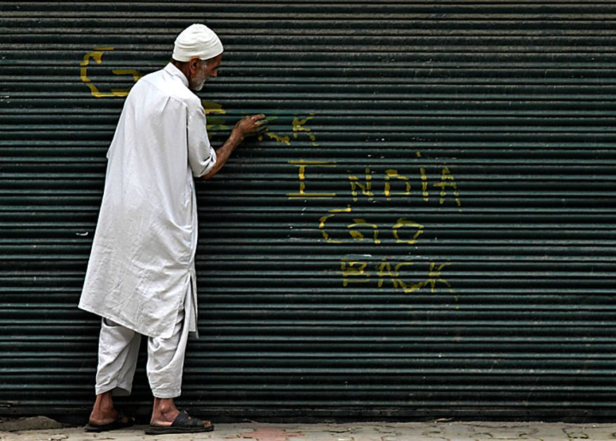 A Kashmiri Muslim paints to hide anti-Indian graffiti written on the shutters of a closed shop during a curfew in Srinagar, India, Monday, Aug. 16, 2010. Thousands of armed police and paramilitary soldiers patrolled nearly deserted streets in Srinagar and other major towns and enforced a strict curfew in most of the Kashmir region Monday. (AP Photo/Mukhtar Khan)