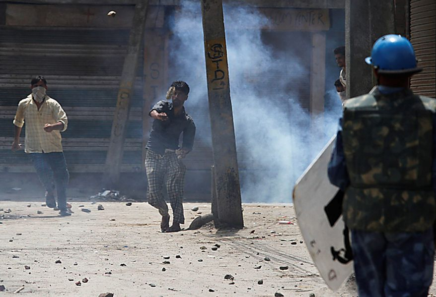 Kashmiri Muslim protesters throw stones at India's Rapid Action Force soldiers during a protest in Srinagar, India, Monday, Aug. 16, 2010. Thousands of armed police and paramilitary soldiers patrolled nearly deserted streets in Srinagar and other major towns and enforced a strict curfew in most of the Kashmir region Monday. (AP Photo/Dar Yasin)