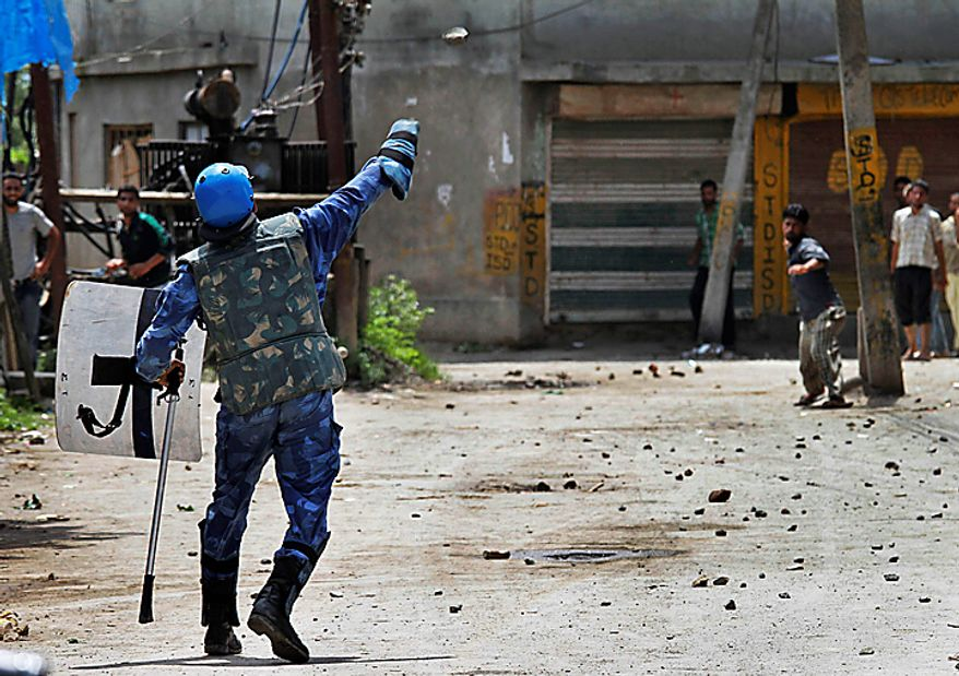 An India Rapid Action Force soldier and Kashmiri protesters throw stones at each other during a protest in Srinagar, India, Monday, Aug. 16, 2010. Thousands of armed police and paramilitary soldiers patrolled nearly deserted streets in Srinagar and other major towns and enforced a strict curfew in most of the Kashmir region Monday. (AP Photo/Dar Yasin)