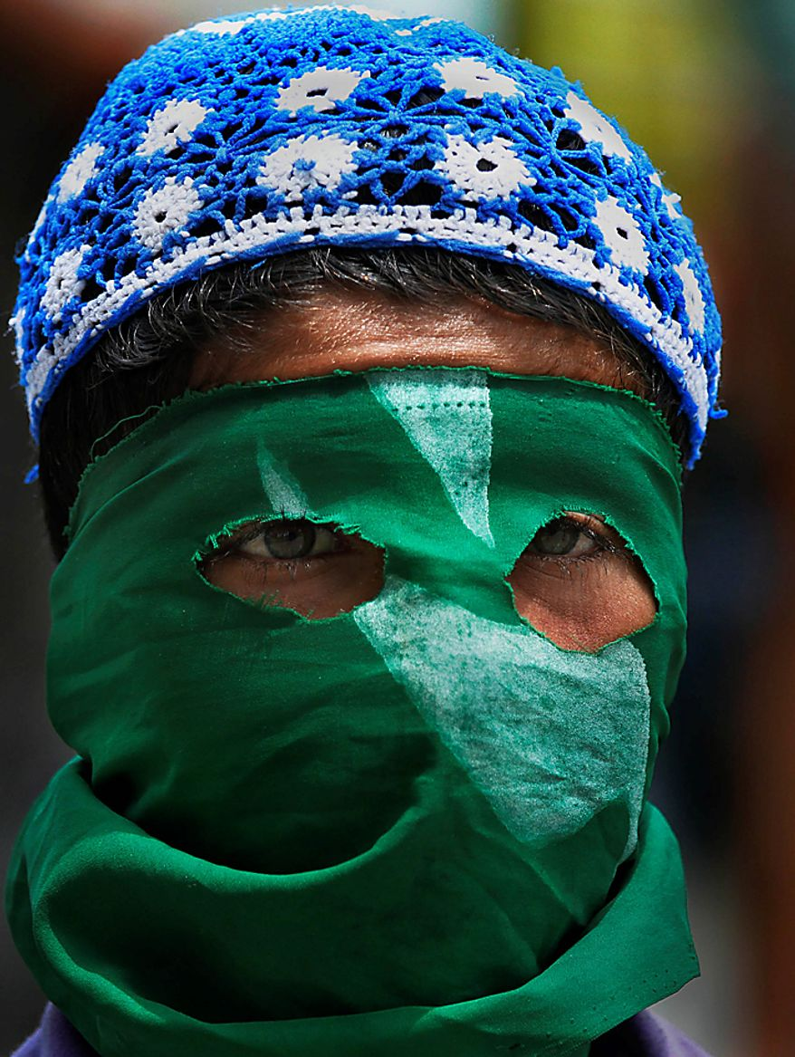 A masked Kashmiri Muslim protester looks on during a protest in Srinagar, India, Monday, Aug. 16, 2010. Thousands of armed police and paramilitary soldiers patrolled nearly deserted streets in Srinagar and other major towns and enforced a strict curfew in most of the Kashmir region Monday. (AP Photo/Dar Yasin)