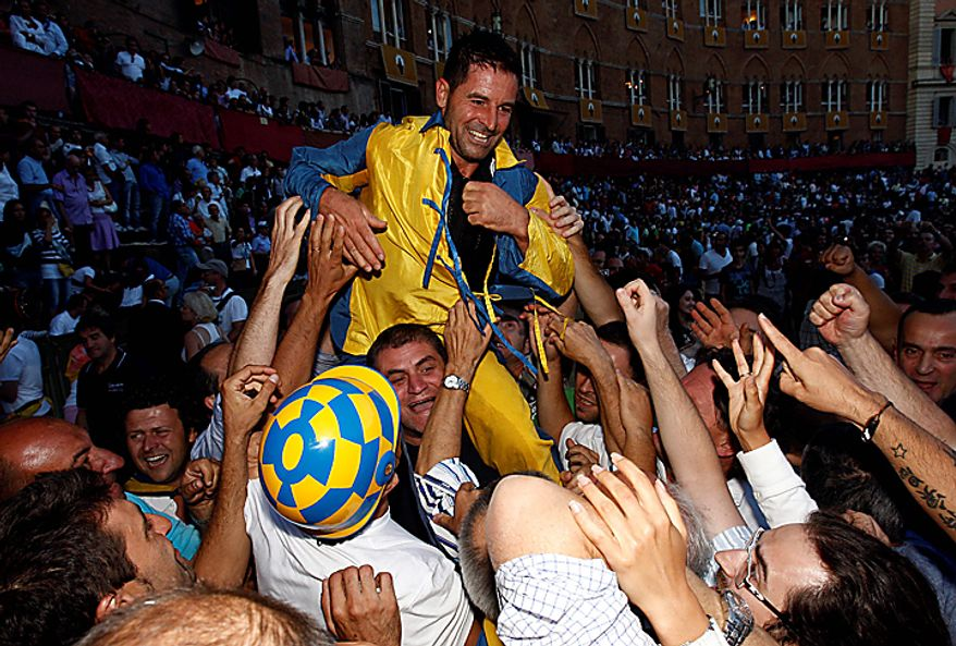 "Luigi Bruschelli ""Trecciolino""  representing the Tartuca neighborhood, celebrates after winning the Palio, the famous break-neck bareback horse race around Piazza del Campo, Siena's main piazza, Italy, Monday, Aug. 16,  2010. The annual Palio pits Siena neighborhoods against one another and its a major tourist draw for this Tuscan city. Each neighborhood puts up a horse and rider to race three times around the slippery, dirt covered cobblestone track. (AP Photo/Paolo Lazzeroni)"