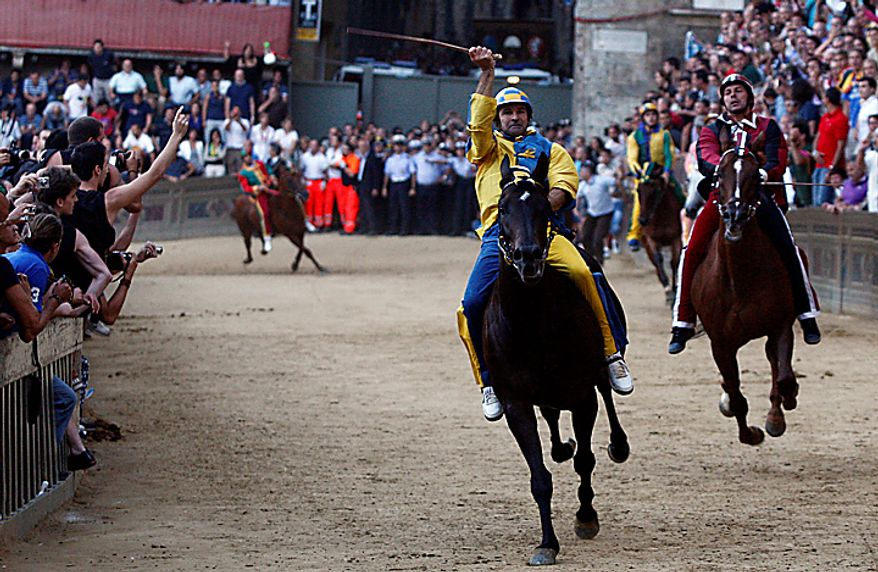 """Luigi Bruschelli """"Trecciolino"""" on  Istriceddu, who represents the Tartuca neighborhood on his way to win the Palio, the famous break-neck bareback horse race around Piazza del Campo, Siena's main piazza, Italy, Monday, Aug. 16, 2010. The annual Palio pits Siena neighborhoods against one another and its a major tourist draw for this Tuscan city. Each neighborhood puts up a horse and rider to race three times around the slippery, dirt covered cobblestone track. (AP Photo/Paolo Lazzeroni)"""