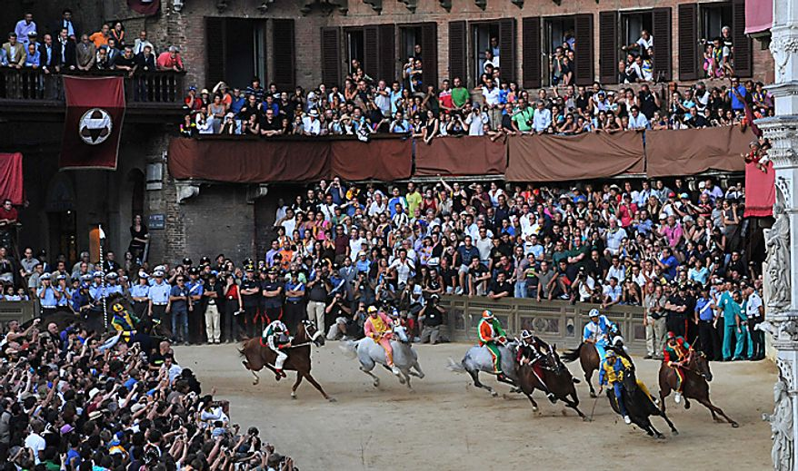 """Luigi Bruschelli """"Trecciolino"""" on  Istriceddu,  second from right, who represents the Tartuca neighborhood on his way to win the Palio, the famous break-neck bareback horse race around Piazza del Campo, Siena's main piazza, Italy, Monday, Aug. 16, 2010. The annual Palio pits Siena neighborhoods against one another and its a major tourist draw for this Tuscan city. Each neighborhood puts up a horse and rider to race three times around the slippery, dirt covered cobblestone track. (AP Photo/Paolo Lazzeroni)"""