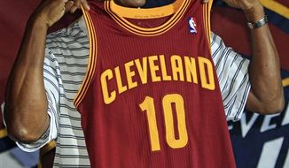 """Former Cleveland Cavaliers' Austin Carr holds up the the Cavs new road uniform, Tuesday, Aug. 17, 2010, in Cleveland. The Cavs' new uniforms, already available on line, will include a """"deeper"""" wine and """"brighter"""" gold hue than their previous jerseys. They will also include the word """"Cleveland"""" written in a block-style lettering as opposed to the script of the past. (AP Photo/Tony Dejak)"""