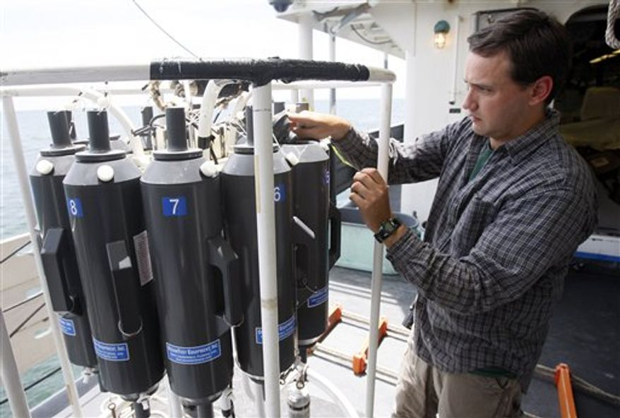 In this Aug. 14, 2010 file photo, survey technician Jim Burkitt adjusts bottles used to capture subsurface water samples on a Conductivity-Temperature-Depth, or CTD, carousel onboard the National Oceanic and Atmospheric Administration research vessel Henry B. Bigelow near the coast of Louisiana, Saturday, Aug. 14, 2010. The vessel is operating near the site of the Deepwater Horizon oil wellhead to collect subsurface water samples for analysis onshore as well as monitor oil and gas seepage on the seafloor. Scientists are giving different estimates on how much oil remains in the ocean and the long terms effects on the environment.  (AP Photo/Patrick Semansky, File)