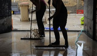 Women clean a flooded house in Aguilar de la Frontera, southern Spain, on Tuesday, Aug. 17, 2010. Three people were killed and two injured in flash floods in towns close to the southern Spanish city of Cordoba, authorities said Tuesday. (AP Photo/Manu Fernandez)