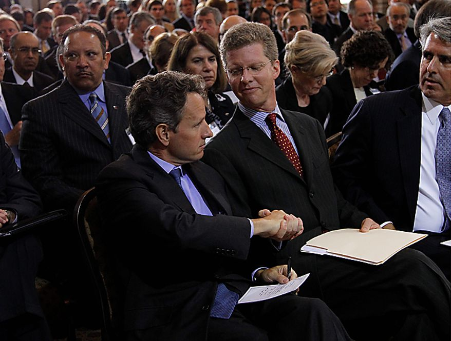 Treasury Secretary Timothy Geithner, left, shakes hands with Housing and Urban Development Secretary Shaun Donovan, right, during the Conference on the Future of Housing Finance, Tuesday, Aug. 17, 2010, at the Treasury Department in Washington. (AP Photo/Pablo Martinez Monsivais)
