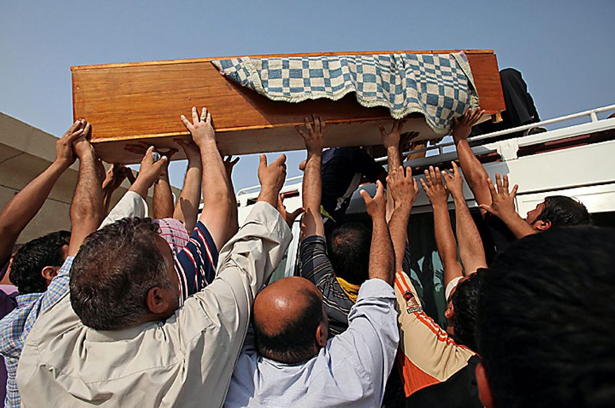 Mourners load the coffin of Sarmd Hamza, 19, onto a vehicle during his funeral in Najaf, south of Baghdad, Iraq, Tuesday, Aug. 17, 2010. Hamza was killed when a suicide bomber sat for hours Tuesday among hundreds of army recruits before detonating nail-packed explosives strapped to his body, killing and wounding dozens of them and casting new doubt on the ability of Iraqi forces as U.S. troops head home. (AP Photo)
