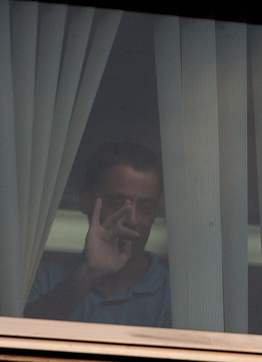 A Palestinian man identified by a Turkish news agency as Nadim Injaz gestures through the window of the Turkish embassy in Tel Aviv, Israel, Tuesday, Aug. 17, 2010. A Palestinian took hostages in the Turkish Embassy in Tel Aviv Tuesday after shots were fired outside, Israeli police and a Foreign Ministry official said, in an incident that appeared to have only an indirect link to recent tensions between the two countries.(AP Photo/Eli Dassa)