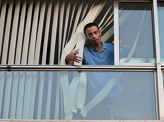 A Palestinian man identified by a Turkish news agency as Nadim Injaz stands in the window of the Turkish embassy in Tel Aviv, Israel, Tuesday, Aug. 17, 2010. A Palestinian took hostages in the Turkish Embassy in Tel Aviv Tuesday after shots were fired outside, Israeli police and a Foreign Ministry offici