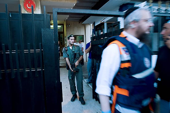 An Israel border police officer holds his weapon as a paramedic rushes put of  the Turkish Embassy in Tel Aviv, Israel, Tuesday, Aug. 17, 2010. A Palestinian took hostages in the Turkish Embassy in Tel Aviv Tuesday after shots were fired outside, Israeli police and a Foreign Ministry official said, in an incident that appeared to have only an indirect link to recent tensions between the two countries. (AP Photo / Ariel Schalit)