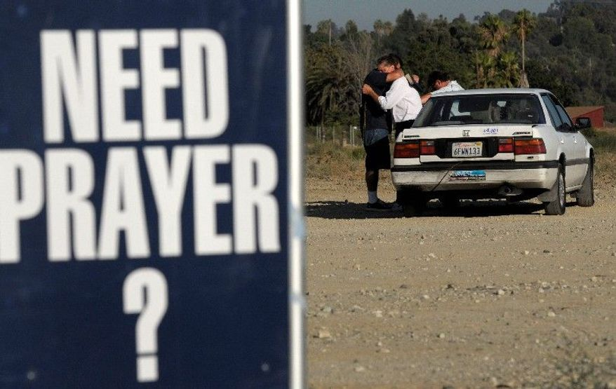 ABOVE: Gary Carerra (left) hugs David Vetsch as the two men pray with Calvin Hart at a car in the lot off Barton Road in Loma Linda. Even in the winter months, motorists stop frequently to pray in the oftentimes rainy, gusty field, says self-appointed spiritual counselor Mr. Heggi.