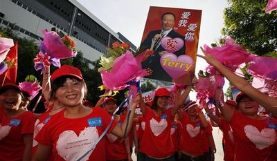 """Foxconn workers hold a picture of Terry Gou, chairman of Foxconn Group, with Chinese characters reading, """"Love Me, Love You,"""" on during a rally to raise morale at the heavily regimented factories inside the Foxconn plant in Shenzhen, south China, Guangdong province, Wednesday August 18, 2010. (AP Photo/Kin Cheung)"""