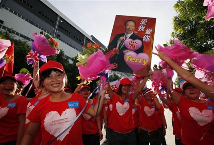 "Foxconn workers hold a picture of Terry Gou, chairman of Foxconn Group, with Chinese characters reading, ""Love Me, Love You,"" on during a rally to raise morale at the heavily regimented factories inside the Foxconn plant in Shenzhen, south China, Guangdong province, Wed"