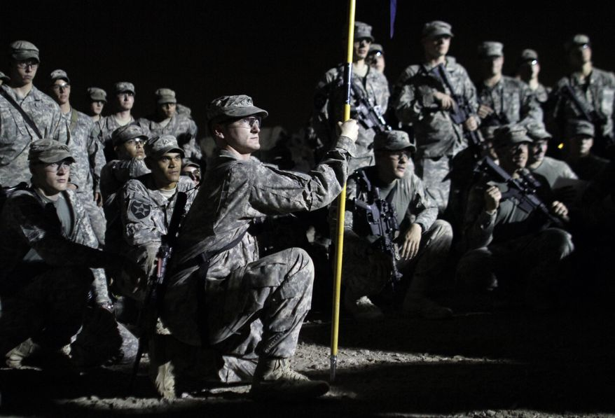 U.S. Army soldiers from C Co., 4th Battalion, 9th Infantry Regiment, 2nd Infantry Division gather Saturday for a formation before driving from Iraq to Kuwait. The soldiers are the last combat brigade to leave Iraq as part of the drawdown of U.S. forces. (Associated Press)