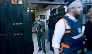 An Israel border police officer stands guard as a paramedic rushes from the Turkish Embassy in Tel Aviv on Tuesday, Aug. 17, 2010. A Palestinian took hostages at the embassy after shots were fired outside, Israeli police and a Foreign Ministry official said, in an incident that appeared to have only an indirect link to recent tensions between the two countries. (AP Photo/Ariel Schalit)